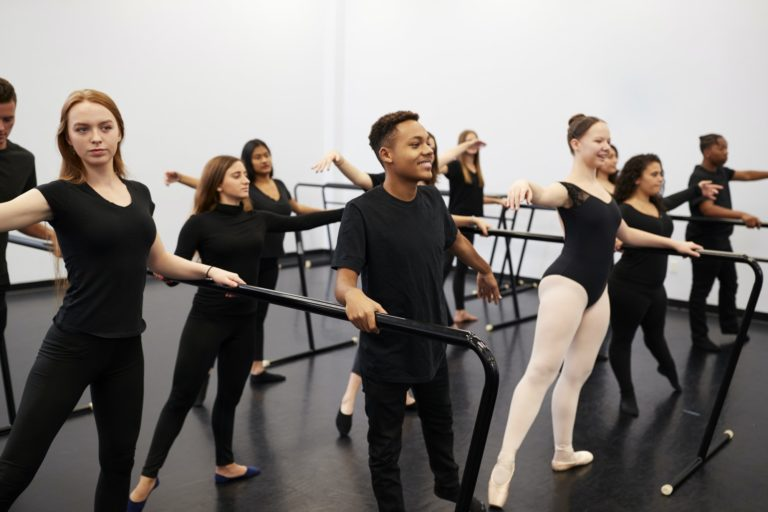 Male And Female Students At Performing Arts School Rehearsing Ballet In Dance Studio Using Barre