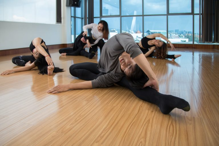 Young dancers stretching with help of trainer